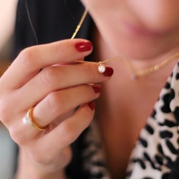 Nätt kort pärlhalsband i guld på stål - guldhalsband för dam | C Stockholm halsband online - hand med ring